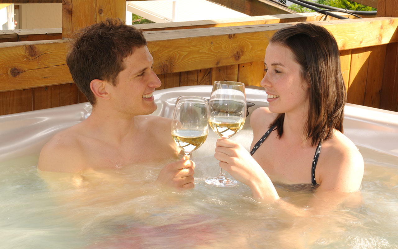 A couple toasting with white wine in a whirlpool