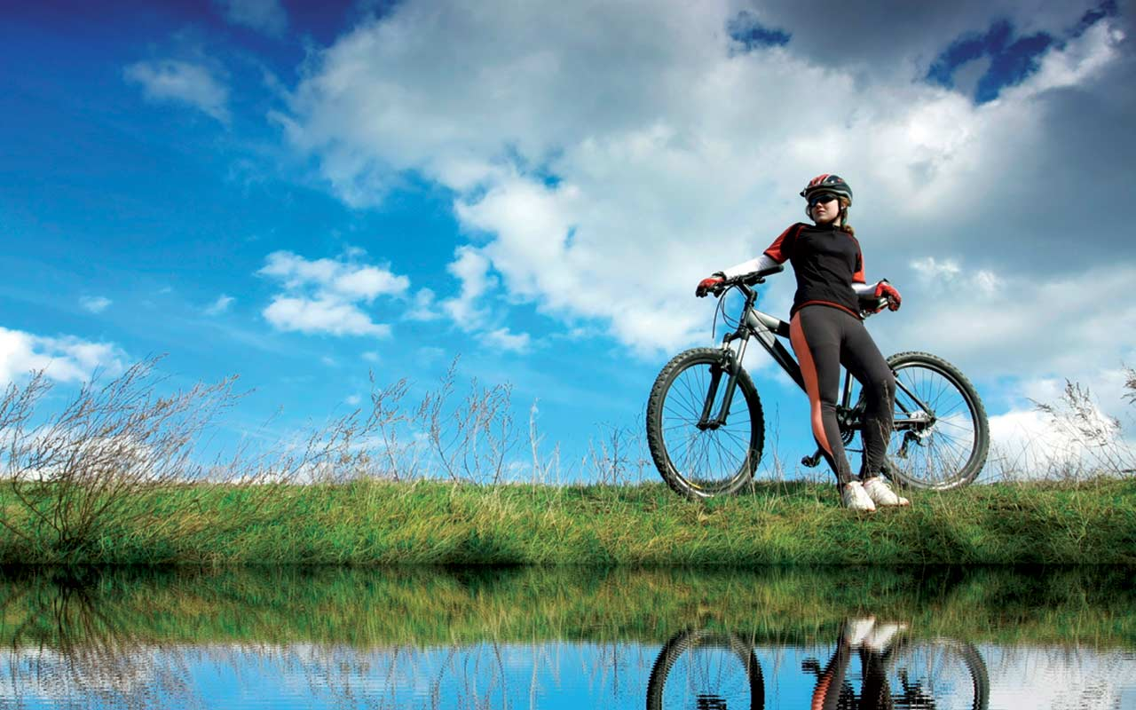 A woman rest on her mountainbike in the shore of a mountain lake
