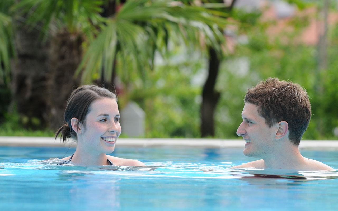 A couple looking in each others eyes while swimming