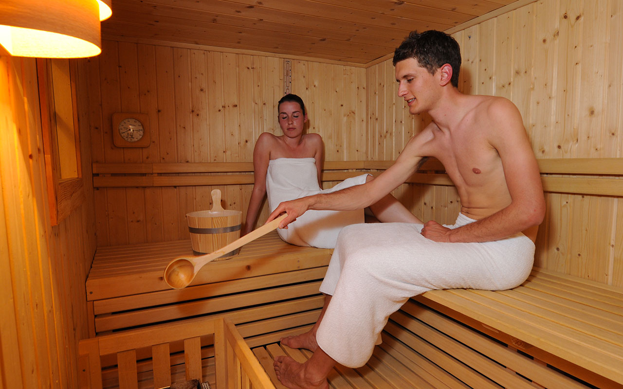 A woman and a man relaxing in a wooden made sauna
