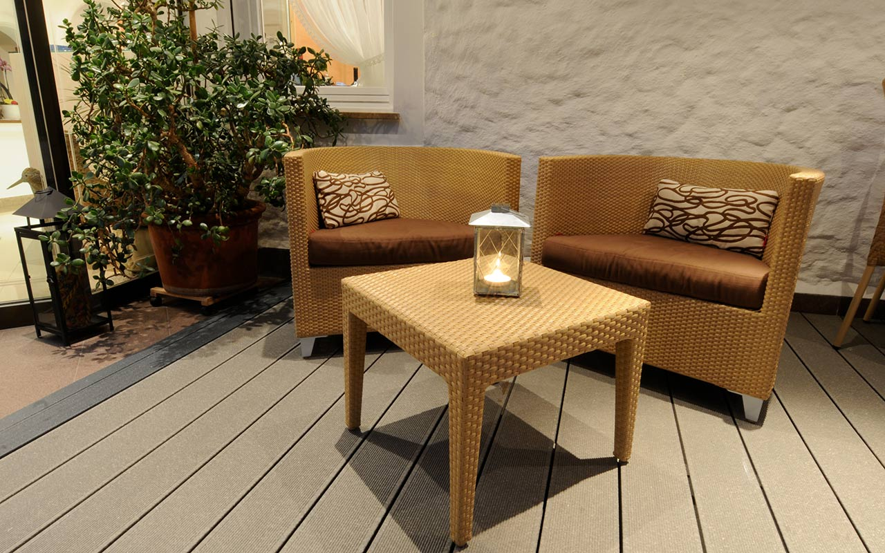 Relax corner with wicker chairs and tables and a lighted candle