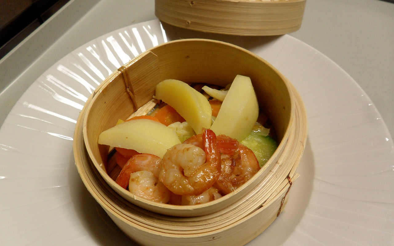 Pawns, potatoes and vegetables cooked in a bamboo container